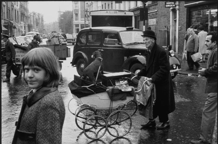 Meanwhile, outside Spitalfields, a man who could have been the inspiration for Steptoe and Son pushes his pram along the street while a young girl gives the photographer a withering glance