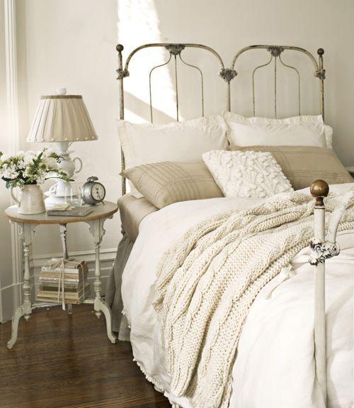 This antique cast-iron bed is dressed in a white cable-knit throw from the Martha Stewart Collection and a white duvet cover by French Laundry Home. A white Anthropologie teacup lamp sits atop the white turned-leg nightstand.