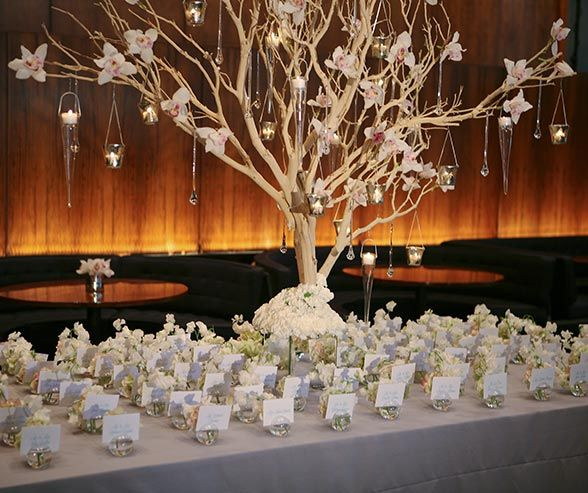 Votive candles in glass baskets serve as a decorative element for this escort card table.