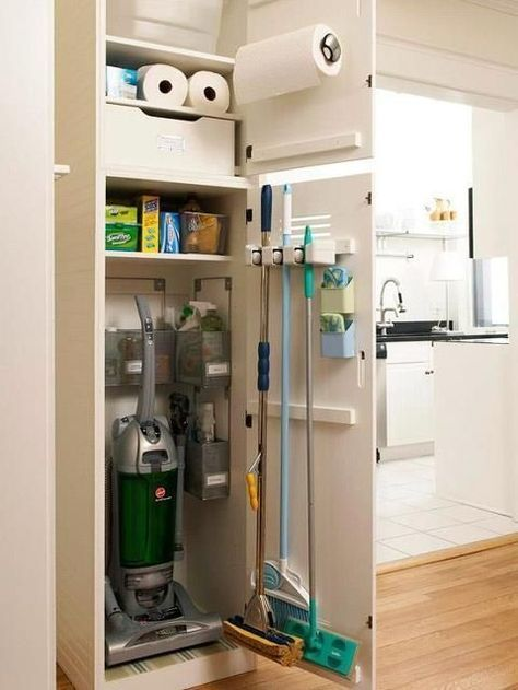 built in utility closet along hallway broom, vacuum, iron, ironing board, cleaning supplies