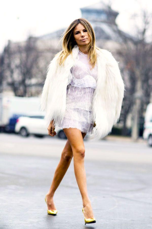 Erica Pelosini wears a white faux fur coat over a mini dress