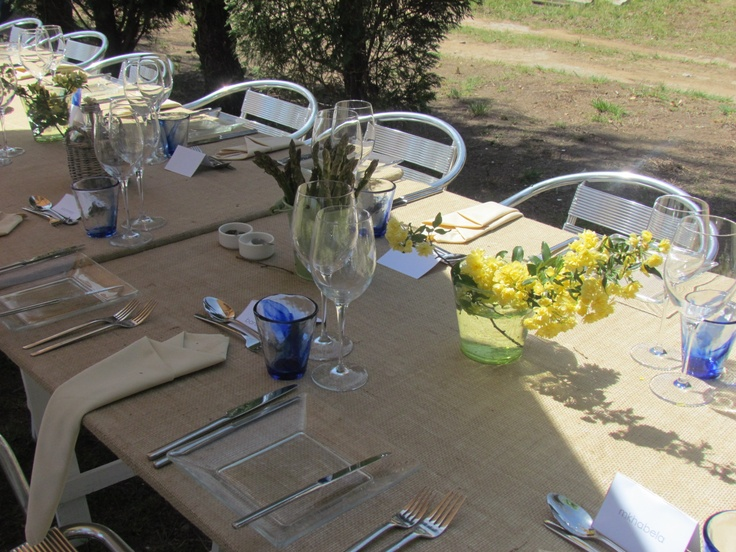 Family style seating; long table tops covered in hessian with wooden trestle legs. Fresh flowers, lettuce & aspargus from the farm for decor.