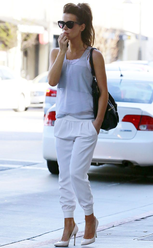 Kate Beckinsale in light blue tank, white Joie crop pants, and white pointed-toe heels, accessorized with cat-eye glasses and black shoulder bag.
