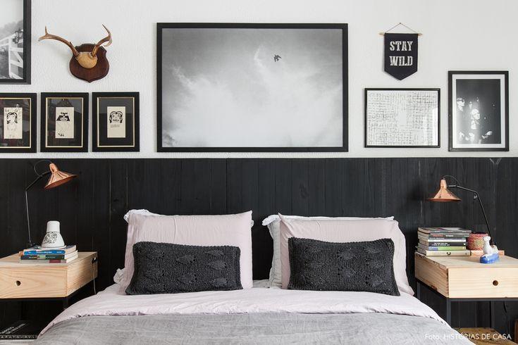 Quarto de casal tem cabeceira de madeira pintada de preto, quadros em tons de cinza e roupa de cama rosa.