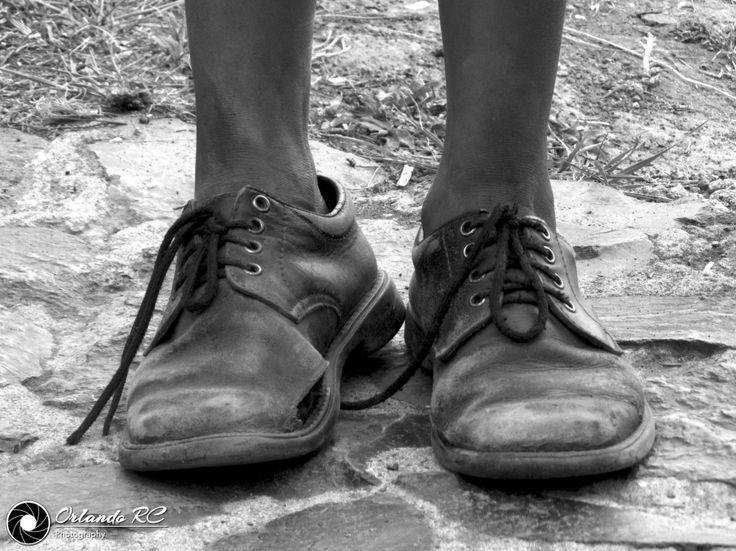 """Los Zapatos de Juan -  Juan y Pedro son dos de once hermanos, que a su corta edad se ganan la vida contando historias a turistas y """"rebuscandose"""". Siempre mal vestidos, sucios y evidentemente acosados por su realidad le hacen frente a la calamidad que les ha tocado vivir. Uno quiere ser astronauta y el otro mecánico, un duro camino les falta por recorrer posiblemente lleno de desilusiones y frustraciones. Espero de todo corazón un día ver que el primer astronauta salvadoreño y que se llame…"""