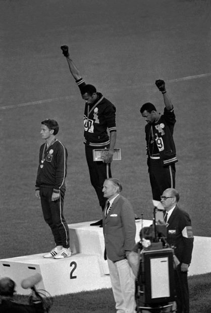 Photo: American athletes Tommie Smith, center, and John Carlos raise their fists and hang their heads while the U.S. national anthem plays during their medal ceremony at the 1968 Summer Olympics in Mexico City. Their black power salute became front page news around the world as a symbol of the struggle for civil rights. To their left stood Australian Peter Norman, who expressed his support by wearing an Olympic Project for Human Rights badge.