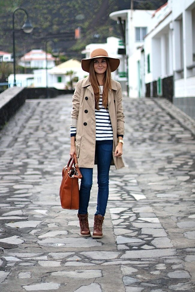 Rock a beige trenchcoat with blue skinny jeans to create a chic, glamorous look. Complement this look with dark brown leather lace-up ankle boots.  Shop this look for $215:  http://lookastic.com/women/looks/hat-crew-neck-sweater-trenchcoat-tote-bag-skinny-jeans-lace-up-ankle-boots-watch/7615  — Khaki Wool Hat  — White and Navy Horizontal Striped Crew-neck Sweater  — Beige Trenchcoat  — Tobacco Leather Tote Bag  — Blue Skinny Jeans  — Dark Brown Leather Lace-up Ankle Boots  — Gold Watch