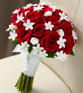 "The FTD® Poetry™ Bouquet has a look of pure elegance and charm that will make you look your bridal best. Red roses are accented with white tulips and white stephanotis blooms, beautifully tied together with a white French taffeta ribbon to give you an appearance that only poetry could describe. Approximately 13""H x 10""W."