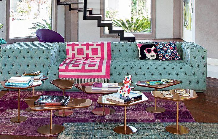 O ponto de partida para a decoração colorida foi o sofá esverdeado. A partir daí, a arquiteta Andrea Murao combinou o tapete roxo e a manta rosa. O resultado é moderno e despojado