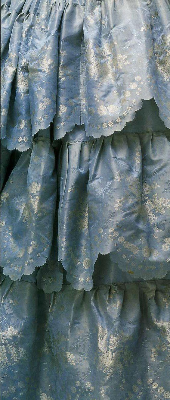 Вечернее платье (деталь). Начало 1850-х. Светло-голубая шелковая тафта-брокад с узором в виде роз, украшение на корсаже спереди из шелкового атласа и тюля, юбка из трех рядов воланов с фестонами по краям.
