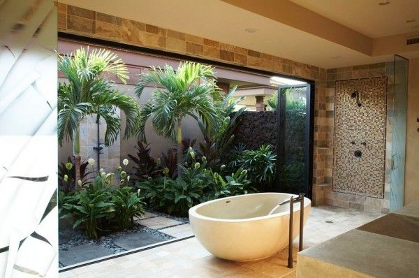 This bathroom enjoys a fuller garden complete with palm trees for a tropical bathing experience; you can even take a shower beneath the fron...