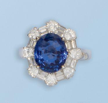 Bague en or gris 18 k stylisant une fleur.  Le pistil est serti d'un saphir ovale, de 5,30 cts.  Les pétales sont formés d'une succession de diamants poires, intercalés de diamants baguettes.  Le saphir est accompagné d'un certificat suisse (GRS) qui stipule les caractéristiques des gisements du Sri Lanka (Ceylan), sans traitement thermique.  Tour de doigt: 53.  Poids brut: 7,9 g   Estimation : 14.100/17.860€