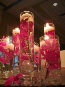 I keep seeing this a lot: submerged flowers in glass cylinders with floating tealights