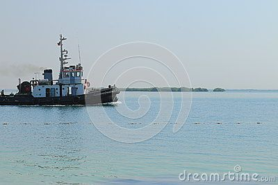 Tugboat moves through calm water of the Bay at noon on a Sunny day