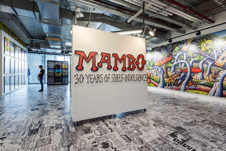 "The entrance to the Mambo exhibition at aMBUSH GALLERY. In the background is part of the ""Millennial Wallscape"" a Reg Mombassa mural commissioned to celebrate the recent 40th anniversary of the Sydney Opera House. It was painted on a construction hoarding for a building site in the Opera House's southern forecourt. (Credit Enzo Amato)"