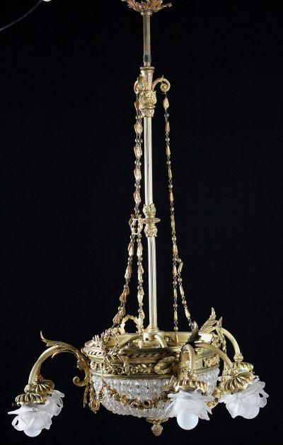 Lampadario in bronzo dorato con corpo centrale con gocce in cristallo. Tre bracci e sei punti luce.