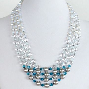 This graceful nautical necklace has the twinkle and soothing palette of an oceanside escape. Its gentle color ombre fades from silver and teal, to clear and aquamarine, and then to milky whitish blue. Created with its four strands of Swarovski crystals, Swarovski glass pearls, rock crystal and iridescent sea opal. Full length 22.5″. SOLD