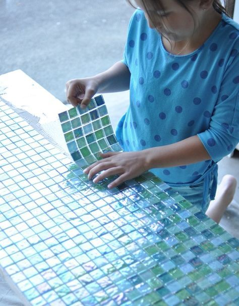 Plywood base and glass mosaic. (Good idea for fixing a broken patio table.)