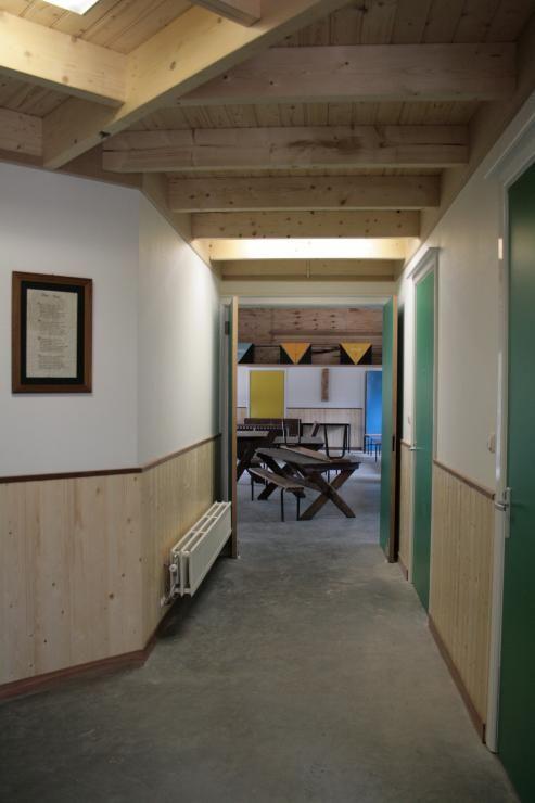 Gang met groene deuren en houten lambrisering