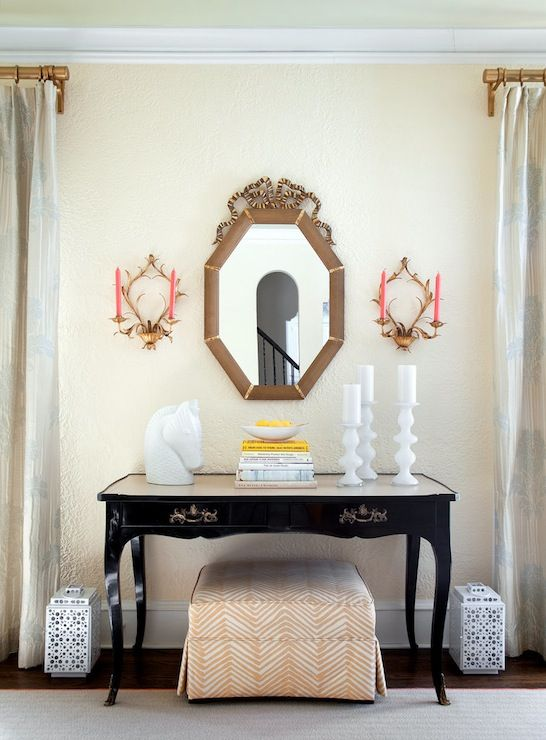 The New York Times - living rooms - gold curtain rod, gray drapes, gray draperies, floor length drapes, floor length draperies, black lacquered console table, cabriole leg black lacquered console, antiqued black lacquered console table, orange and white skirted ottoman