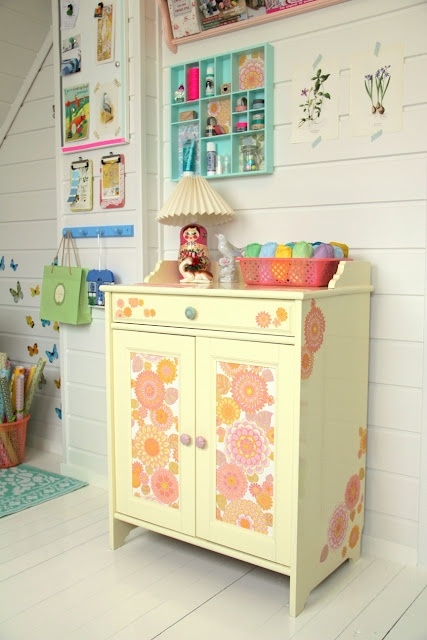 """This is actually an old stained IKEA dresser that I have painted a pale yellow and wallpapered . On the front are whole sections of paper, while the sides, top drawer are flowers from the wallpaper I cut out and glued on. I used wallpaper paste to attach everything."""