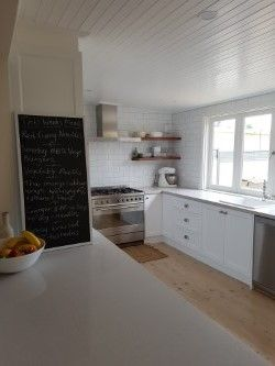 Classic White Kitchen. Shaker style doors. White Subway tile with grey grout. Wooden floating shelves. Grey iron bark shelves. Nordic Loft Caeserstone. Lime washed timber floors. Kitchen Black board. V-joint ceiling. Bi-fold windows.90cm Smeg Oven. IKEA sink and tapware.