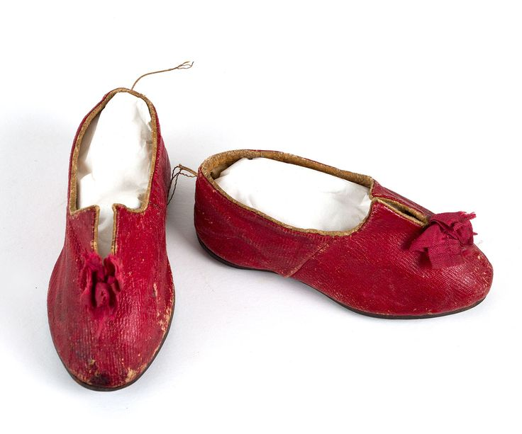 Child's shoes c.1810. Made from red leather and lined with beige linen, the shoes sport delightful red ribbon rosettes. The upper edges are bound with tan leather. The soles are of brown leather. Vintage Textiles $875