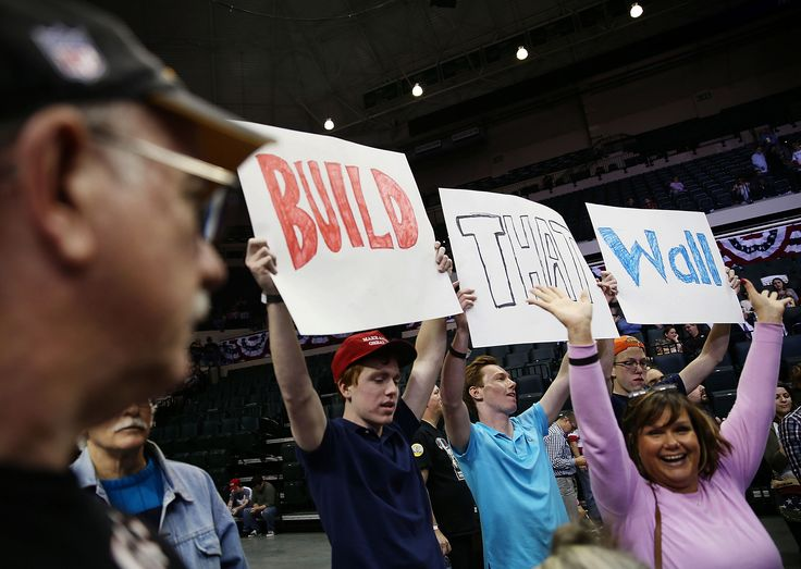 "TAMPA, FL - FEBRUARY 12: People hold signs that read, "" Build that Wall"", as they wait for the start of a campaign rally for Republican presidential candidate Donald Trump at the University of South Florida Sun Dome on February 12, 2016 in Tampa, Florida. The process to select the next Democratic and Republican Presidential candidate continues.  (Photo by Joe Raedle/Getty Images)"