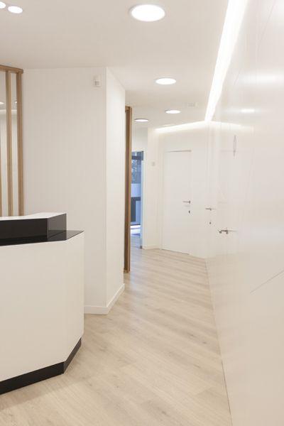 Reforma de Clínica Dental en Barcelona. Pintando paredes y panelando en color blanco unificamos el espacio, además de ordenarlo. Con esta intervención damos amplitud a la clínica y conseguimos que sea vea un espacio con más continuidad.  Al final el resultado es una clínica amplia, elegante y ordenada, dando confianza y seriedad. Al mismo tiempo se percibe un punto aséptico y clínico, como debe ser un espacio sanitario.