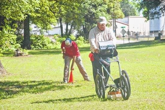 Len Strozier, right, and his son, Brandon, of Omega Mapping Services scan the grounds of the Confederate Cemetery on Miller Street using ground penetrating radar. Strozier was hired by the Troup County Historical Society to detect unmarked graves in the cemetery.