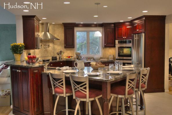 Transitional Kitchen-  Corner sink, raised cabinet to hide sink from living area, corner stove, corner double ovens, stainless steel appliances, pot filler faucet at cooking station, large table style counter height seating for five, stained cherry wood cabinets, granite countertops