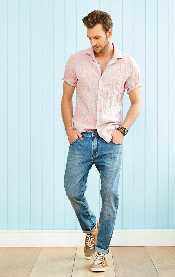 Tall male model wearing loose jeans and a light pink short sleeved shirt.