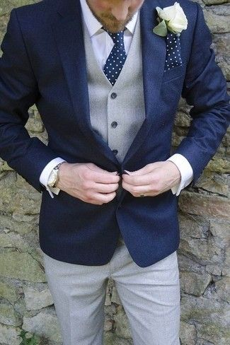 Navy blazer, white dress shirt, grey vest and trousers complimented by a navy tie with white polka dots and a matching pocket square.
