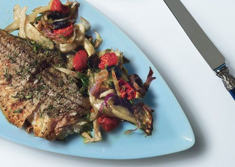 """Roasted Striped Bass with Fennel, Tomatoes, and Oil-Cured Olives Some Italian cooks would never combine cheese and seafood, but feel free to grate a little Pecorino Romano over the striped bass before serving. """"In Puglia, fish and cheese go together,"""" says restauranteur Donatella Arpaia."""