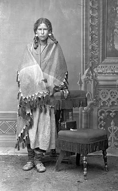 SUMMARY Unindentifed girl found with Gros Ventre, full length standing studio portrait with painted backdrop, wearing earrings, braided hair, shawl wrapped around shoulders, and moccasins; believed to have been a captive.1880-1890. Barry, D. F. 1854-1934. (David Frances),
