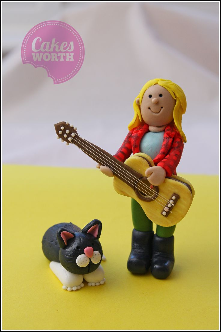 Fondant cake topper. Young girl with her guitar and cat.