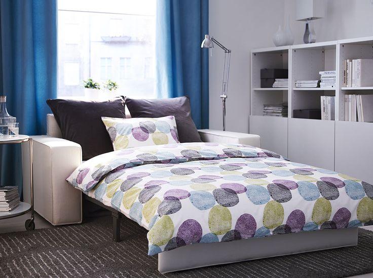Sala com sofá-cama de dois lugares em tecido bege, com combinação de arrumação em branco com portas