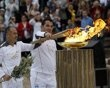Greek veteran weighlifter Piros Dimas (R) and Chinese gymnast Li Ning light a cauldron with the Olympic Flame inside the marble Panathenaic stadium in Athens May 17, 2012.