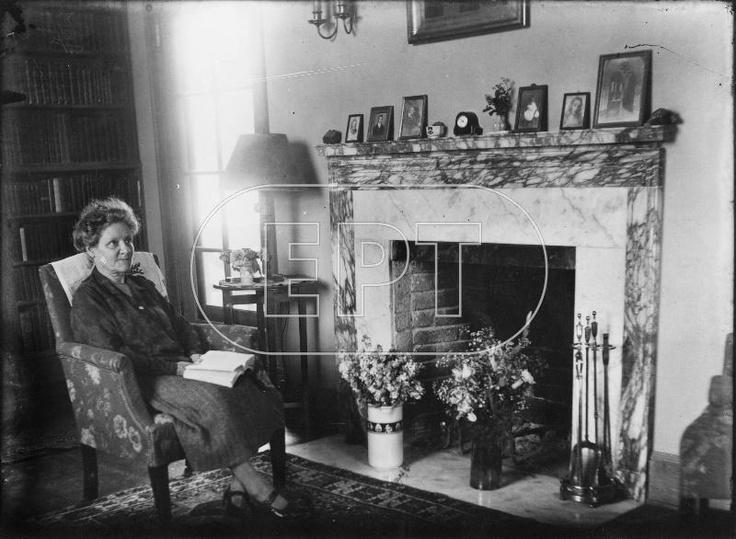 Η ΚΥΡΙΑ SCOGGIN, ΣΥΖΥΓΟΣ ΤΟΥ ΠΡΩΤΟΥ ΔΙΕΥΘΥΝΤΗ ΤΗΣ ΓΕΝΝΑΔΕΙΟΥ ΒΙΒΛΙΟΘΗΚΗΣ, ΣΤΟ ΕΣΩΤΕΡΙΚΟ ΣΠΙΤΙΟΥ. ΚΑΘΙΣΜΕΝΗ ΜΠΡΟΣΤΑ ΣΕ ΤΖΑΚΙ ΜΕ ΒΙΒΛΙΟ ΣΤΑ ΧΕΡΙΑ. Παρασκευή, 1 Ιανουαρίου 1926 (Απο το ψηφιακο αρχειο της ΕΡΤ)