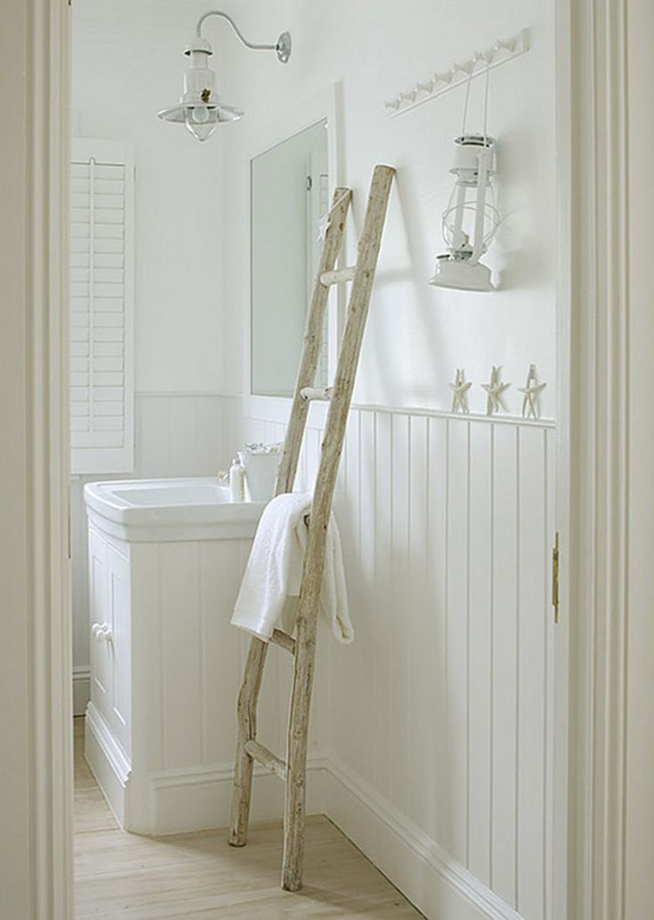 Witte houten badkamer met shutters en houten ladder als handdoekrek.