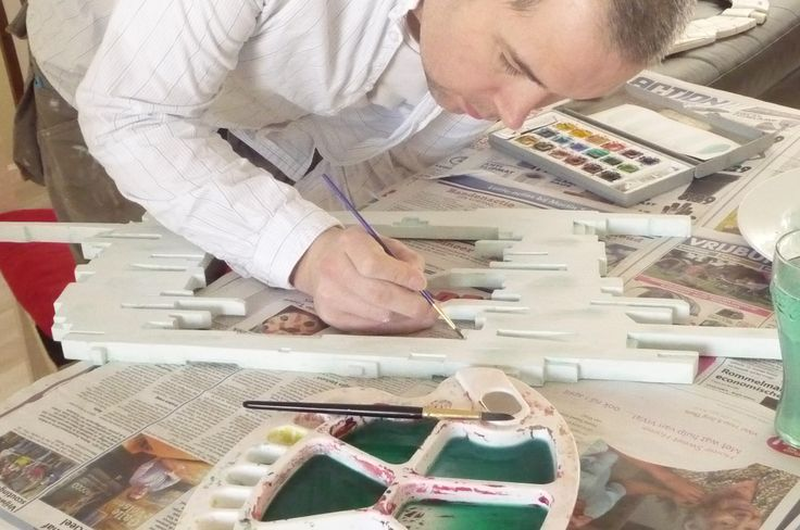 """Hand painting in the fine details of the """"stretched"""" mirror."""