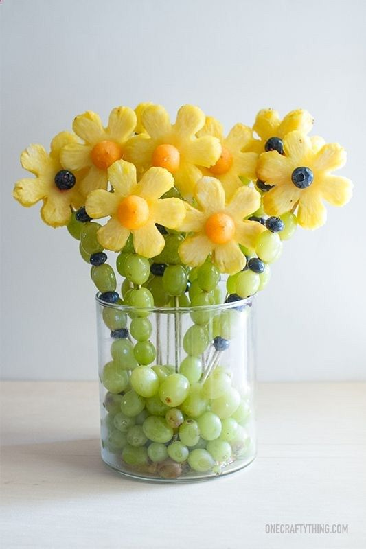 Fruity Flowers~T~ The kids love these and they are beautiful on the table. Use Pineapple, Cantaloupe, Grapes and Blueberries. All you need is a flower cookie cutter, a melon baller and skewers. Could change it up with watermelon and strawberries too.