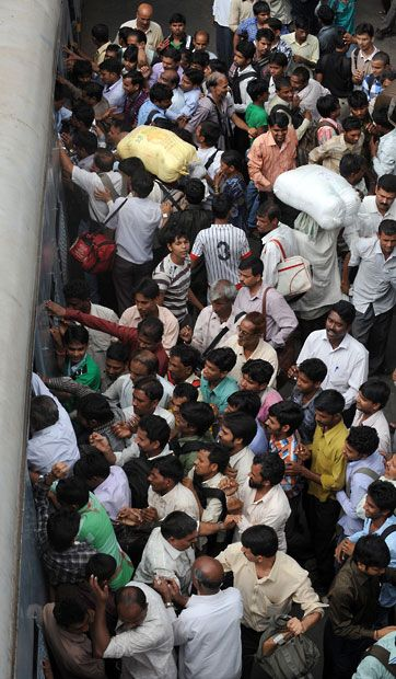 Commuters try to board an overcrowded suburban railway train on the Central Railway line in Mumbai.