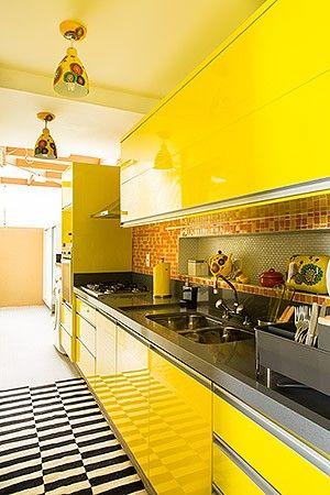 Cozinha | Armários com laca amarela predominam  no ambiente, com bancada de quartzo cinza, da  Massimo. Pastilhas Lepri, na De Stijl, revestem a  parede com nicho, criado no nivelamento de  pilares. Pendente, bule e torradeira comprados em  Praga. Passadeira da By Kamy (Foto: Edu Castello):