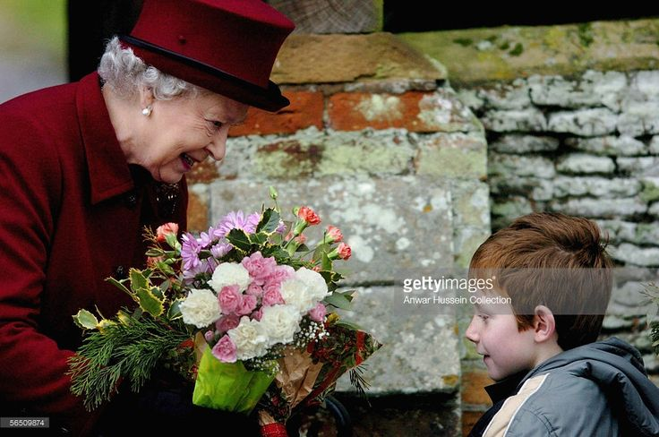 Britain's Queen Elizabeth II smiles as she is given flowers after attending St Mary Magdalene Church, alongside the Countess of Wessex and the Duke of Edinburgh on January 1, 2006, at Sandringham, England.