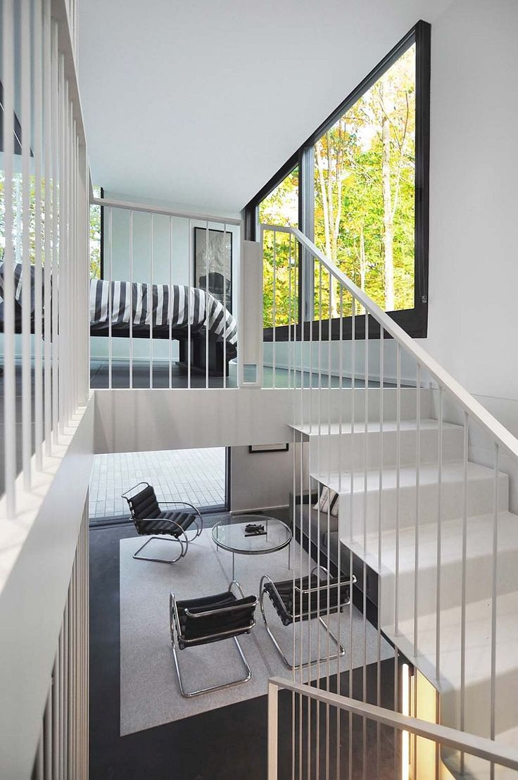 Delicate and sculptural staircase leads to the master bedroom on the top level overlooking the forest