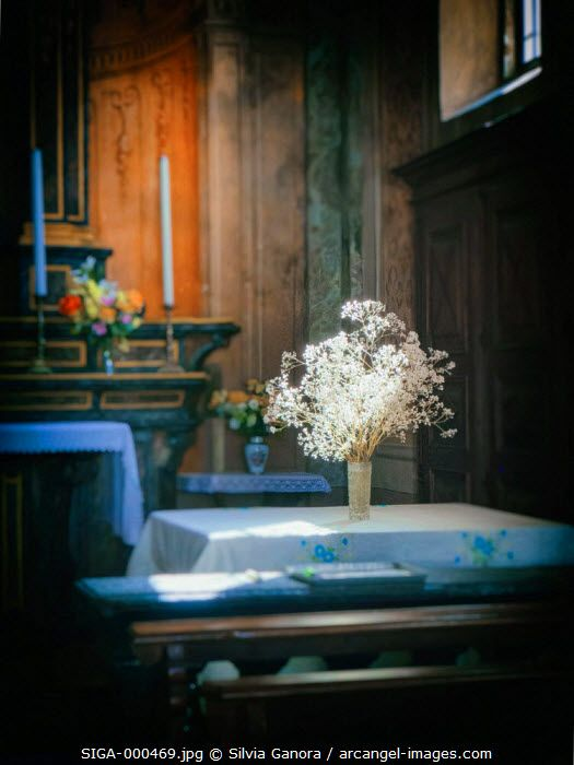 Church interior with bouquet of white flowers on table. Slant of light from window and vignette blur- ©Silvia Ganora Photography - All Rights Reserved  #bookcovers #flowers
