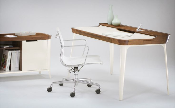 The Herman Miller Airia Desk sports a dual-level white laminate desk top with a walnut frame, aluminum legs, cork-lined trays, and built-in cable management. $2200