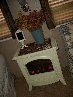 Small electric fireplace painted white and used as a nightstand. Clever.