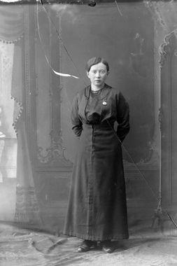 Studioportrett av en kvinne i en mørk kjole. Fotografering 1910 - 1918 Fotograf:Magdalene Norman